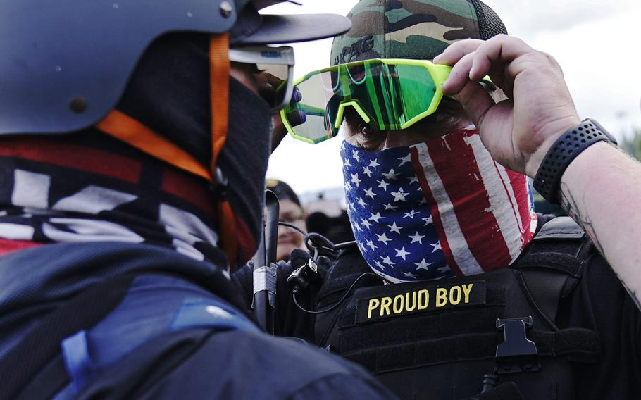 In this Sept. 26, 2020, file photo, a member of the Proud Boys, right, stands in front of a counter protester as members of the Proud Boys and other right-wing demonstrators rally in Portland.