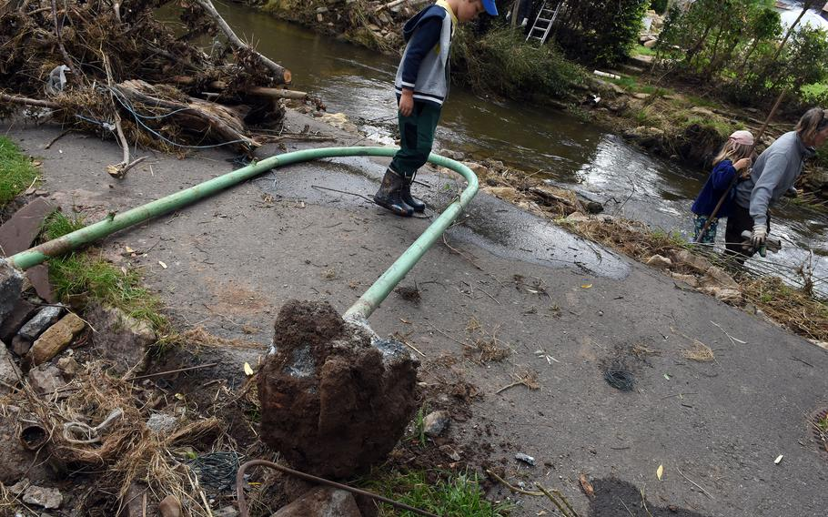 A boy steps over a metal pole uprooted during the severe floods in mid-July along the Nims River in Rittersdorf, Germany, on July 31, 2021.