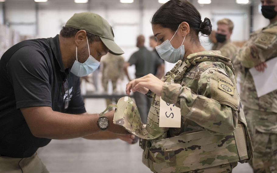 In this image provided by the U.S. Army, Sgt. Katiushka Rivera, a soldier assigned to the 82nd Airborne Division, gets fitted for a modular scalable vest (MSV) during a fielding event in Fort Bragg, N.C., on Sept. 13, 2021.