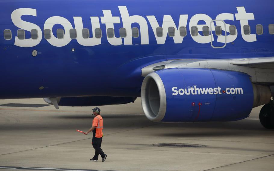 A worker directs a Southwest Airlines Boeing 737 passenger jet pushing back from a gate at Midway International Airport in Chicago on Oct. 11, 2021.