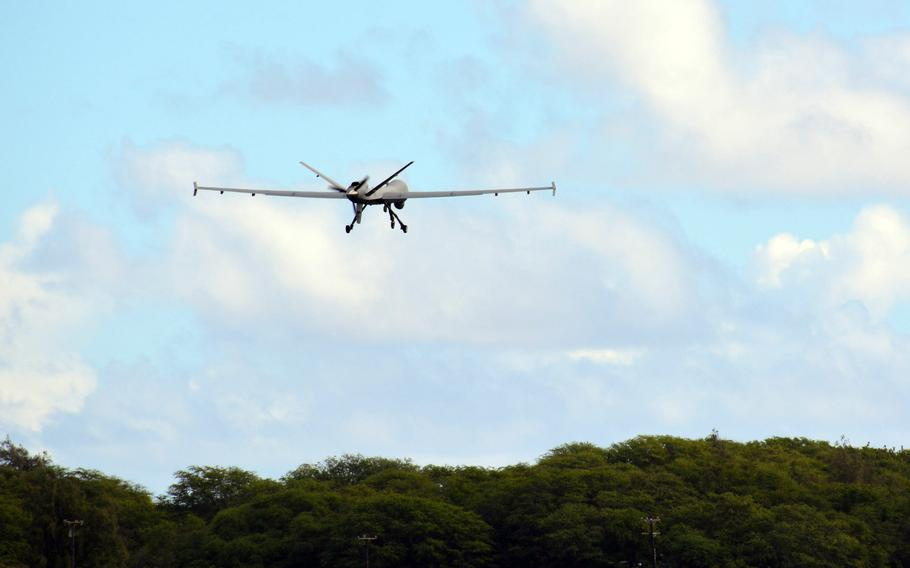An Air Force MQ-9 Reaper drone flies over the tree line at Marine Corps Base Hawaii during Exercise ACE Reaper, Monday, Sept. 27, 2021.