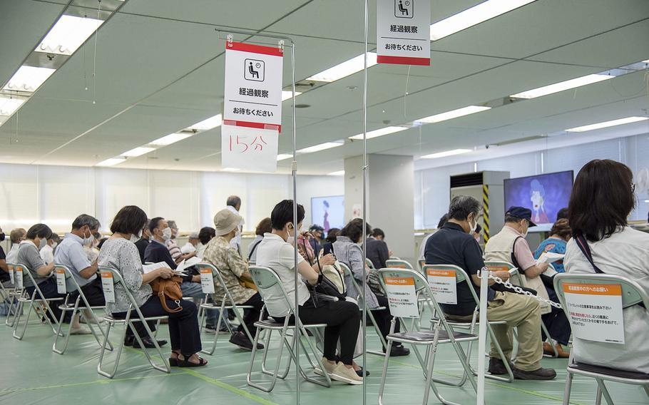 人々は2021年6月9日、東京大手町の日本の陸上自衛隊が主催する注射クリニックでModerna COVID-19ワクチンを接種された後、15分を待ちます。