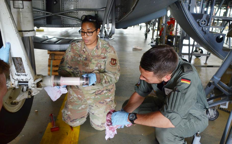 Air Force Tech Sgt. Hazel Cochran, left, cleans the axle of a C-130J's nose landing gear wheel as showing German military academy cadet Tom Palzer how to remove a tire from the plane at Ramstein Air Base on July 15, 2021.