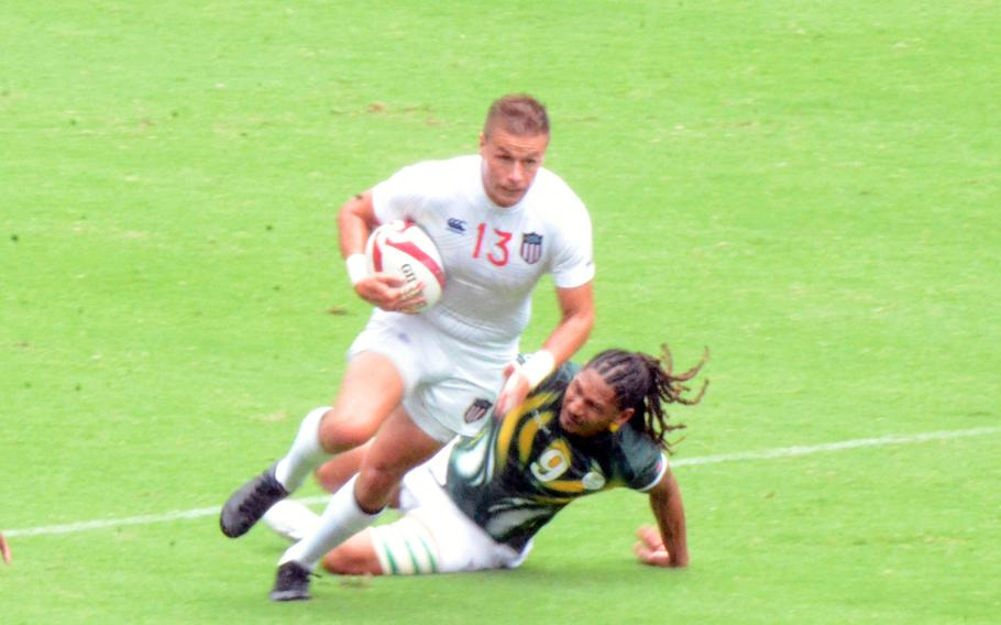 Cody Melphy, a former U.S. Army bridge engineer, breaks a tackle in the U.S. Eagles' Olympic rugby sevens game against South Africa, Tuesday, July 27, 2021.
