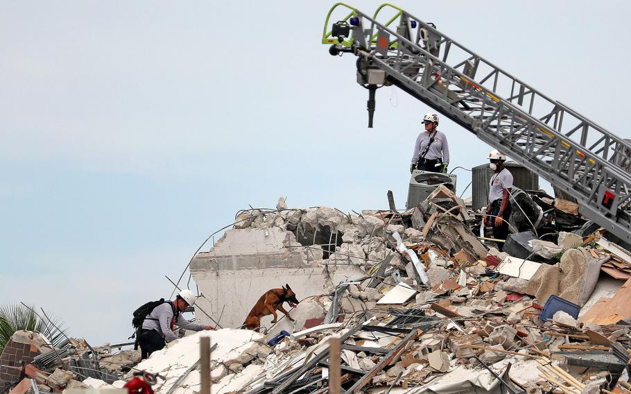 Search and rescue workers along with K-9 units search the site of the 12-story oceanfront Champlain Towers South Condo in Surfside, Fla.
