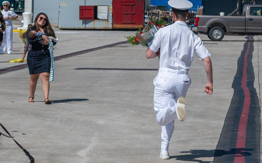 Alex Souter sprints down the dock to wife Daniela Souter as she holds their newborn son, George. He was among seven fathers who got to meet their new babies for the first time as the crew disembarked from the ship.