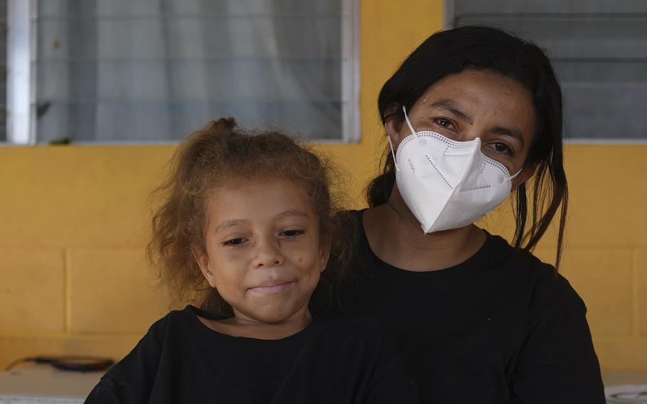 """Asylum-seeker from Honduras, Carla Leiva, 32, holds her five-year-old daughter Zoe as they pose for a photo at the """"Casa del Migrante"""" shelter for migrants in El Ceibo, Guatemala, Thursday, Aug. 12, 2021."""