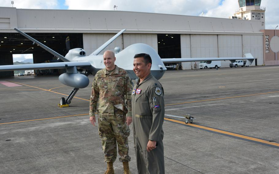 Col. Ryan Keeney, left, commander of the 49th Wing, and Lt. Col. Jaime Olivares, commander of the 9th Attack Squadron, both based at Holloman Air Force Base, N.M., pose near a Reaper drone at Marine Corps Base Hawaii, Monday, Sept. 27, 2021.