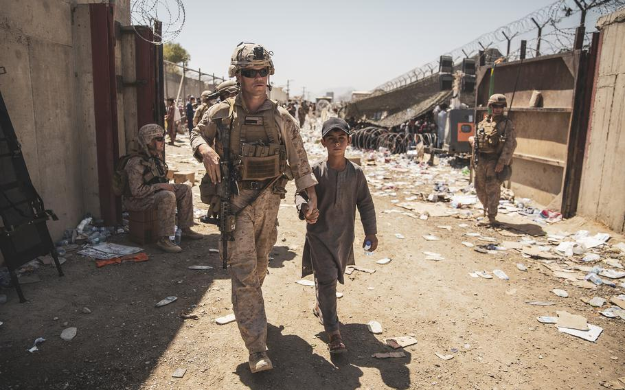A U.S. Marine escorts a young evacuee at Hamid Karzai International Airport in Kabul, Afghanistan, Aug. 24, 2021.