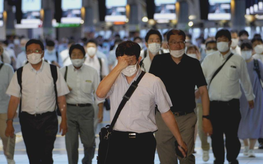 Commuters depart Shinagawa Station in central Tokyo around 7 a.m. Aug. 20, 2021.