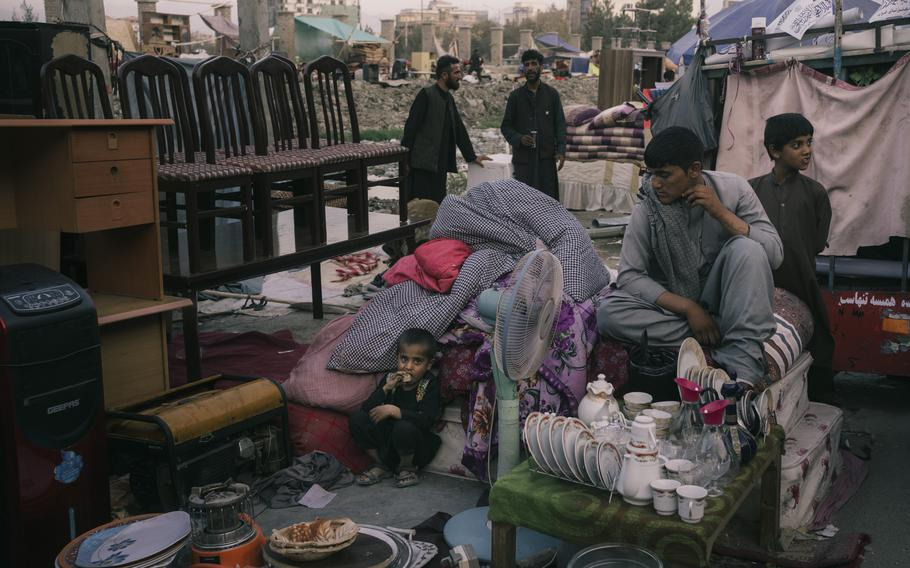 A family waits for buyers in a sprawling market near Ghazi Stadium.