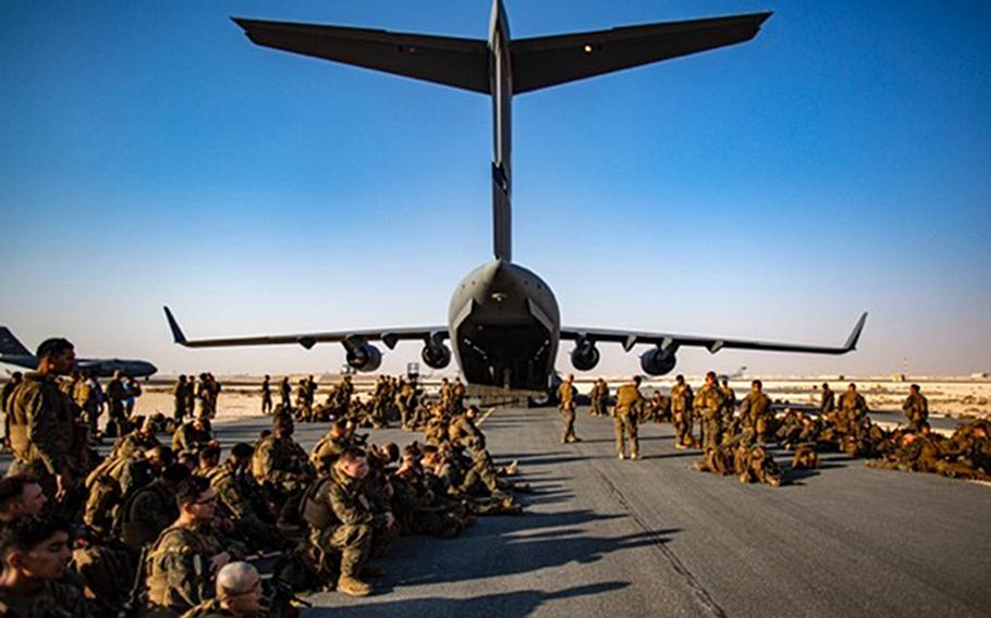Marines assigned to the 24th Marine Expeditionary Unit await a flight at Al Udeid Air Base, Qatar, Aug. 17, 2021. Personnel at the base are working to airlift and house people arriving from Afghanistan.