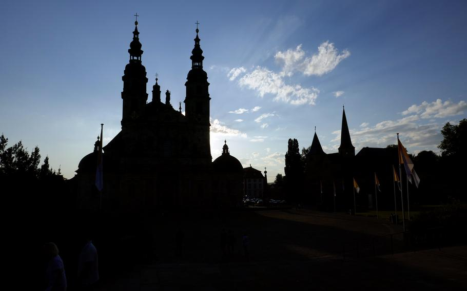Fulda's Baroque basilica, left, and St. Michael's Church are silhouetted in the setting sun. The former was built in the early 18th century, while the latter is 900 years older.