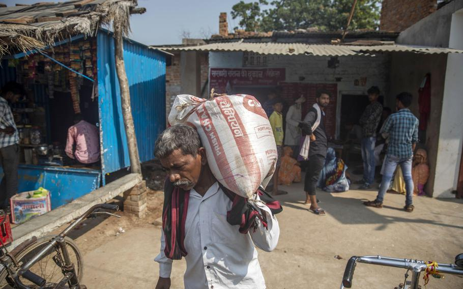 A man carries a sack of food at a state-run ration store in Banda District, Uttar Pradesh, India, on Oct. 12, 2020.