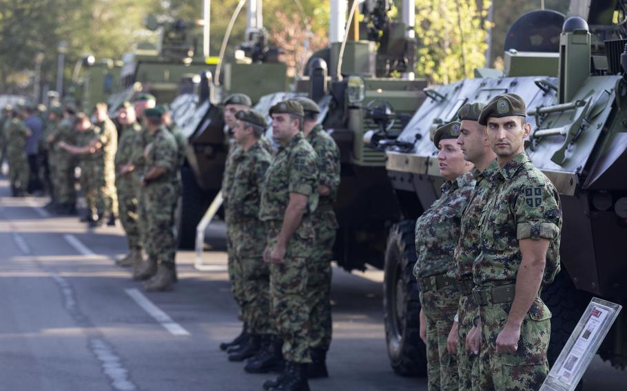 """Serbian army soldiers stand to attention in front of armored personnel carriers on display as part of a newly established """"Serbian Unity Day"""" holiday in Belgrade, Serbia, Wednesday, Sept. 15, 2021."""