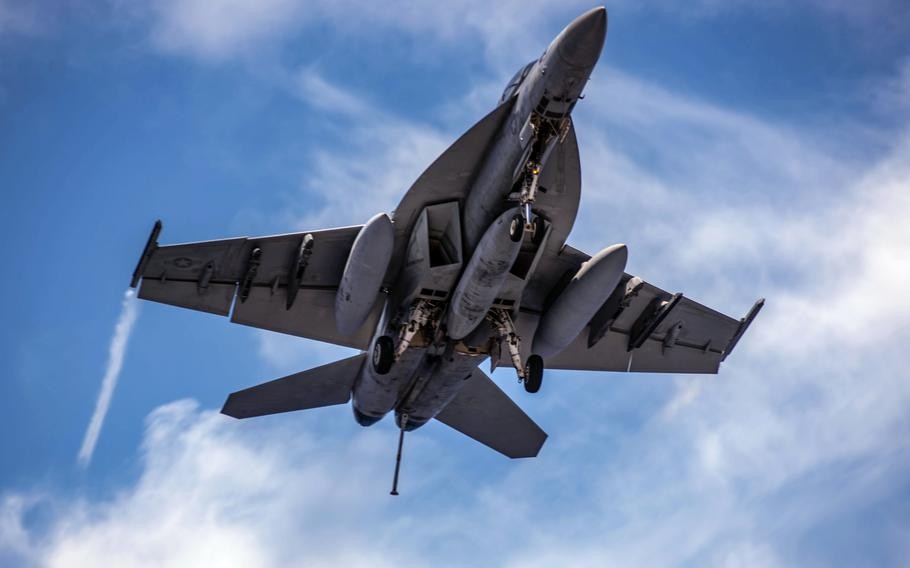 In a May 28, 2021 photo, an F/A-18F Super Hornet attached to the Diamondbacks of Strike Fighter Squadron 102 flies over the flight deck of the USS Ronald Reagan.
