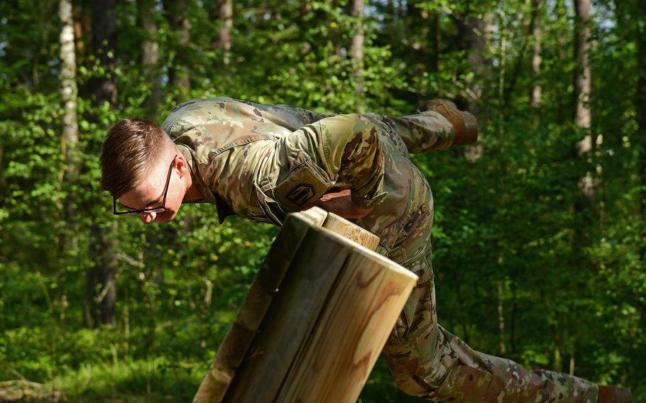 Spc. Shaun Lewis, of the 41st Field Artillery Brigade, jumps over a wall while participating in the obstacle course circuit during the U.S. Army Europe and Africa Best Warrior Competition in Grafenwoehr, Germany, Aug. 9, 2021. Lewis took the title of best soldier in the competition.