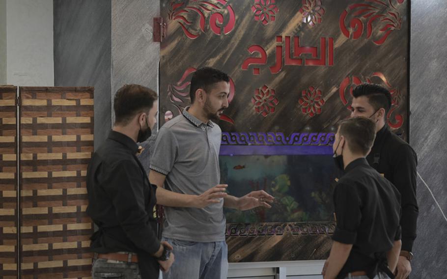 Omar Abukarsh, owner of Fresh Food, talks to the staff inside the Gaza City restaurant Sunday, May 23, 2021.