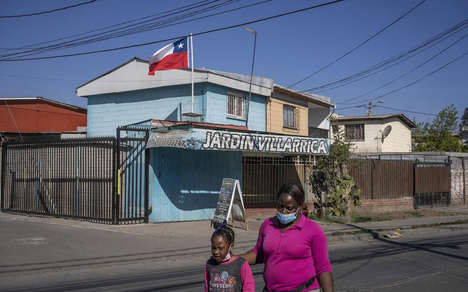 A Haitian woman and girl walk down the street in Quilicura, a neighborhood in Santiago, Chile, known as Little Haiti.