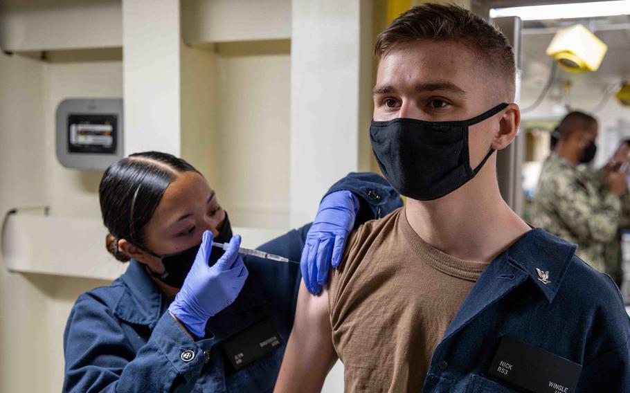 Seaman Jlyn Bautista administers a COVID-19 vaccine to Petty Officer 3rd Class Nicholas Wingle aboard the amphibious transport dock ship USS Arlington, April 23, 2021.