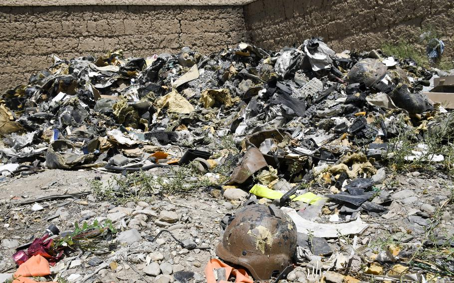 A helmet from Bagram Airfield, Afghanistan, sits in front of a pile of ruined helmets at a trash yard outside the base June 5, 2021. Departing U.S. and NATO troops have crushed most of their discarded trash.