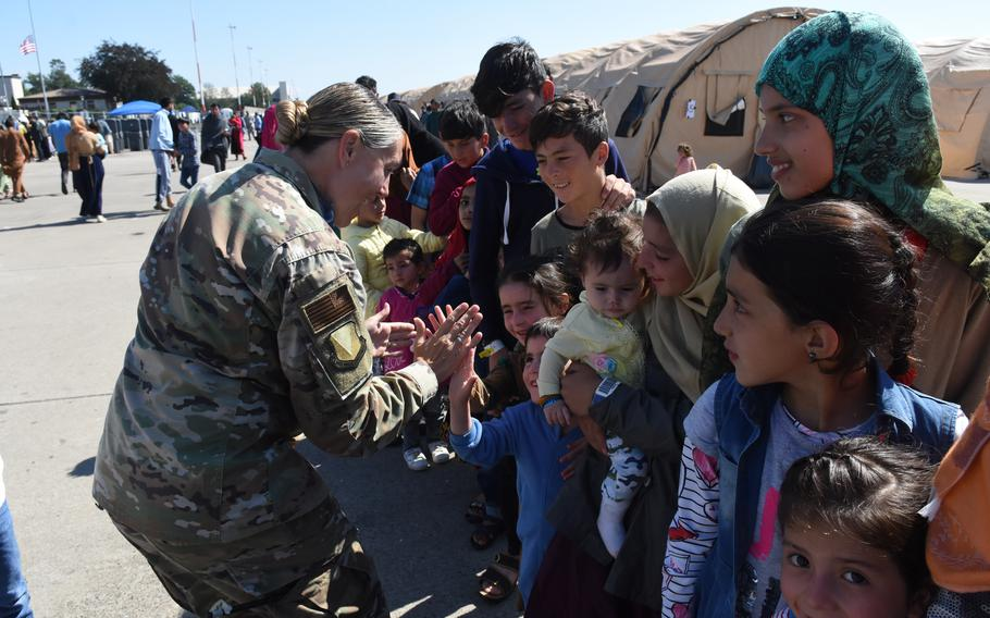 Air Force Col. Amy Glisson exchanges high-fives with Afghan children inside temporary living facilities at Ramstein Air Base, Germany, for evacuees from Afghanistan, Sept. 2, 2021.