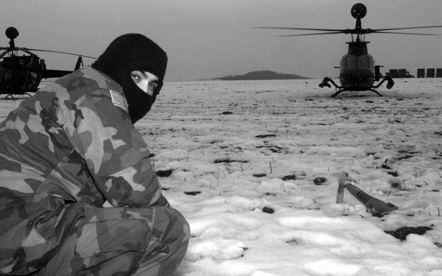 Taszar AB, Hungary, January, 1996: An American IFOR member crouches low just before an attack helicopter takes off from its snowy landing strip.