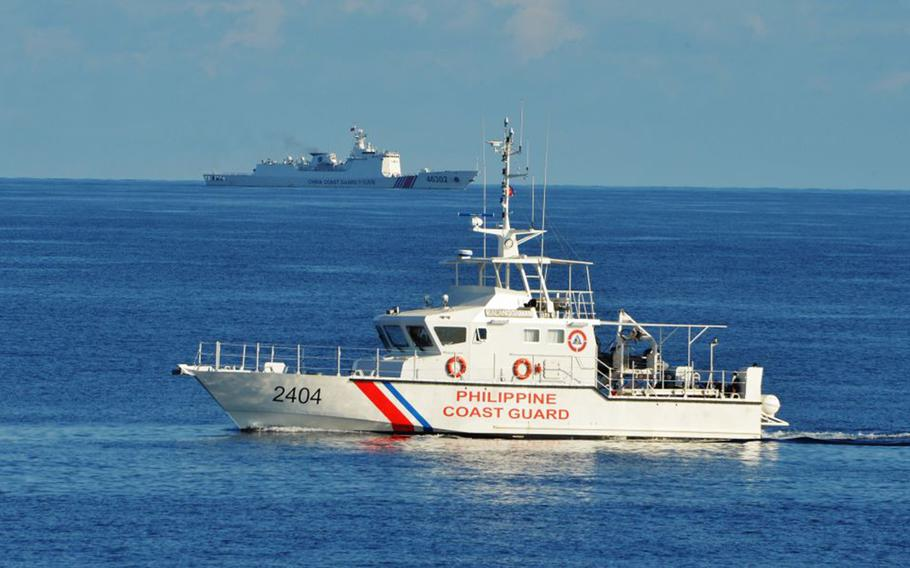 This photo taken on May 14, 2019, a Philippine coast guard ship (right) sails past a Chinese coast guard ship during a joint search and rescue exercise between Philippine and US coast guards near Scarborough shoal, in the South China Sea, on May 14, 2019.