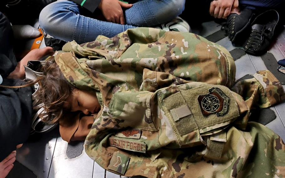 An Afghan child sleeps on the cargo floor of a U.S. Air Force C-17 Globemaster III, kept warm by the uniform of the C-17 loadmaster, during an evacuation flight from Kabul, Afghanistan, Aug. 15, 2021.