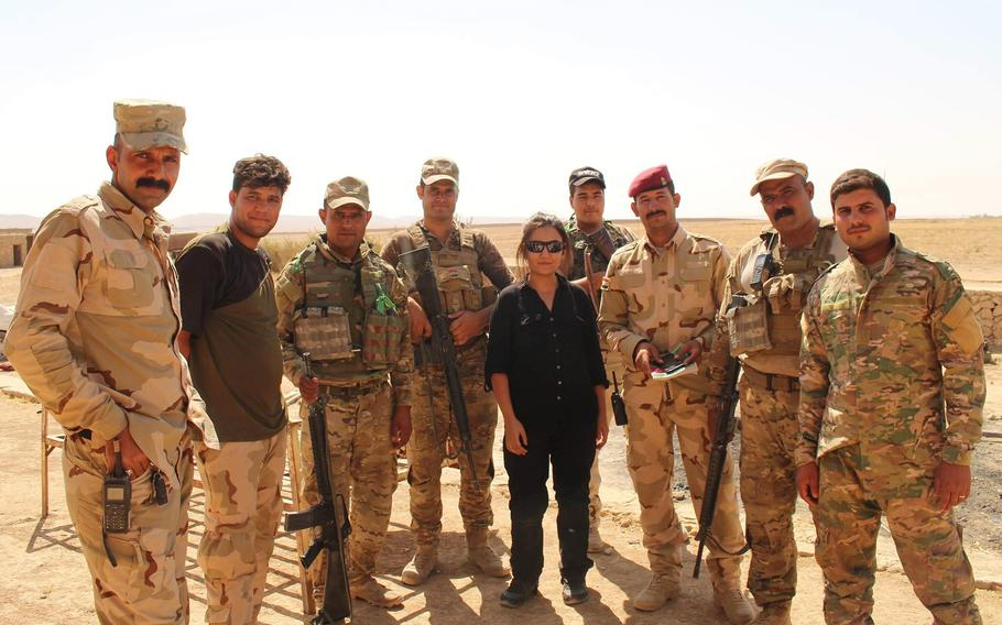 Zainab Olivo poses with Iraqi troops while working as an interpreter and translator for Stars and Stripes during the Battle of Mosul in 2017.