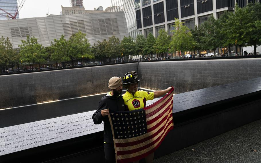 """Retired Santa Clara firefighter Darrell Sales, right, and fellow cyclist Jeremy Provancher, left, stand beside the south pool holding an American flag after completing their """"Bay to Brooklyn"""" bicycle ride at the National September 11 Memorial & Museum, Thursday, Sept. 9, 2021, in New York."""