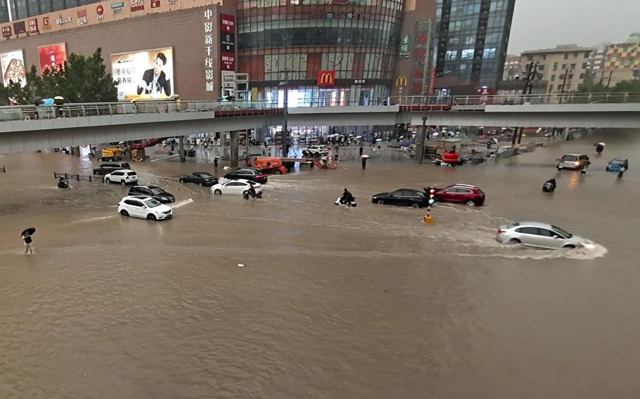 Vehicles are stranded after a heavy downpour in Zhengzhou city, central China's Henan province Tuesday. Heavy flooding has hit central China following unusually heavy rains, with the subway system in Zhengzhou inundated with rushing water.