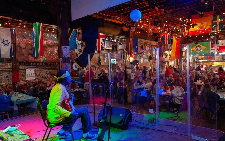 A musician performs behind plexiglass inside a venue at the Juke Joint Festival in Clarksdale, Miss., on April 17, 2021.