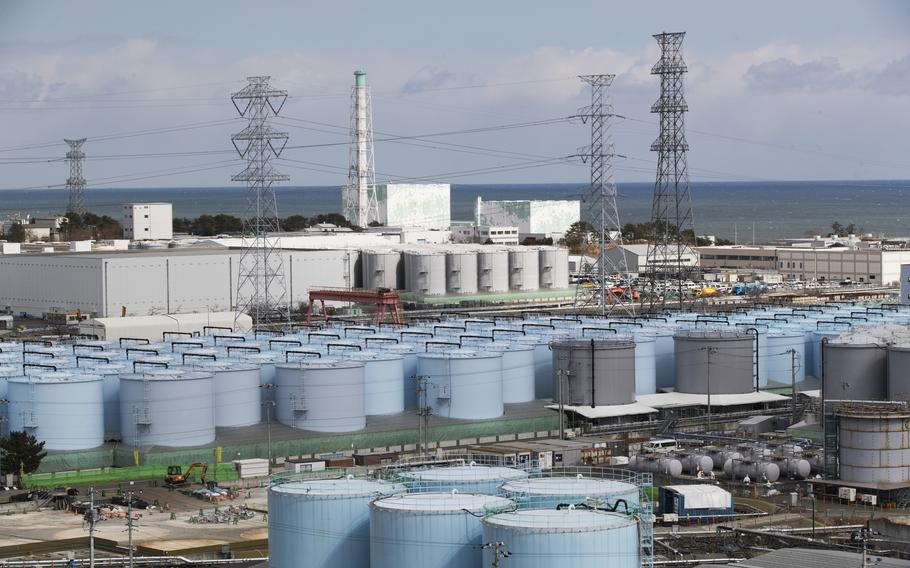 Nuclear reactors of No. 5, center left, and 6 look over tanks storing water that was treated but still radioactive at the Fukushima Daiichi nuclear power plant in Okuma town, Fukushima prefecture, northeastern Japan, Feb. 27, 2021.
