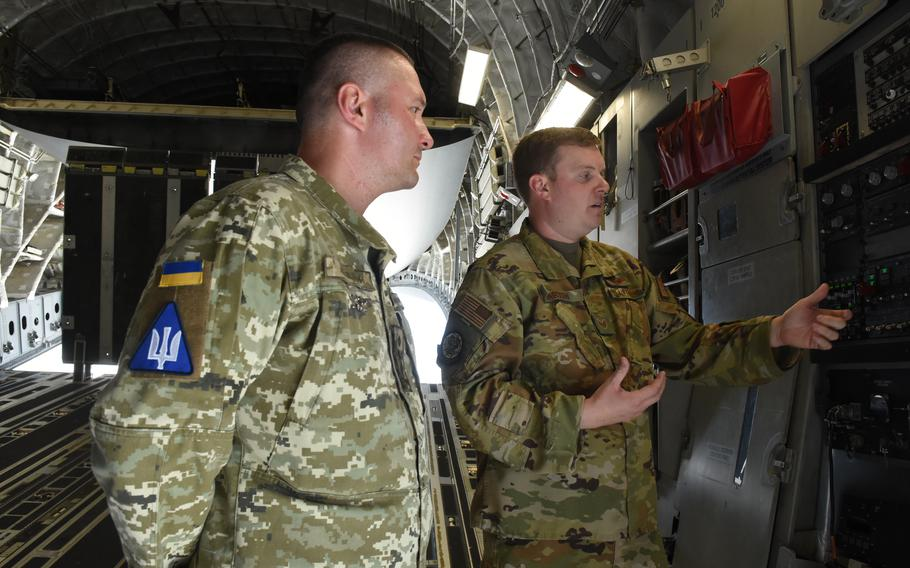 Staff Sgt.  Breck Martin, air advisor and C-17 loadmaster with the 435th Emergency Response Support Squadron, shows Col. Dmytro Lapitskyi, a Ukrainian Air Force air controller and former bomber pilot, the hydraulic system on the back of a C-17 aircraft at Ramstein Air Base, Germany.