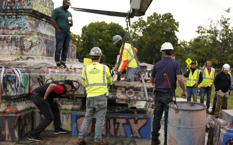 Crews move a section of the base as they attempt to locate a time capsule said to be buried in the base of the statue of on Monument Avenue in Richmond, Va., Thursday, Sept. 9, 2021. The statue was removed from the pedestal on Wednesday.