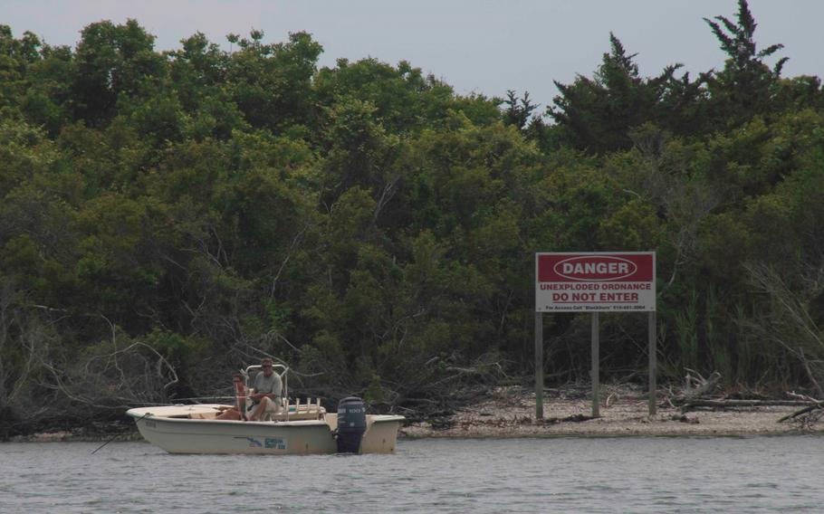 A couple sits illegally anchored in front of Brown's Island in the Atlantic‐Intracoastal Waterway on May 25, 2018. The recent discovery of a hidden 250-pound bomb has prompted a new round of warnings from the Marine Corps for people to avoid setting foot on Brown's Island on the North Carolina coast.