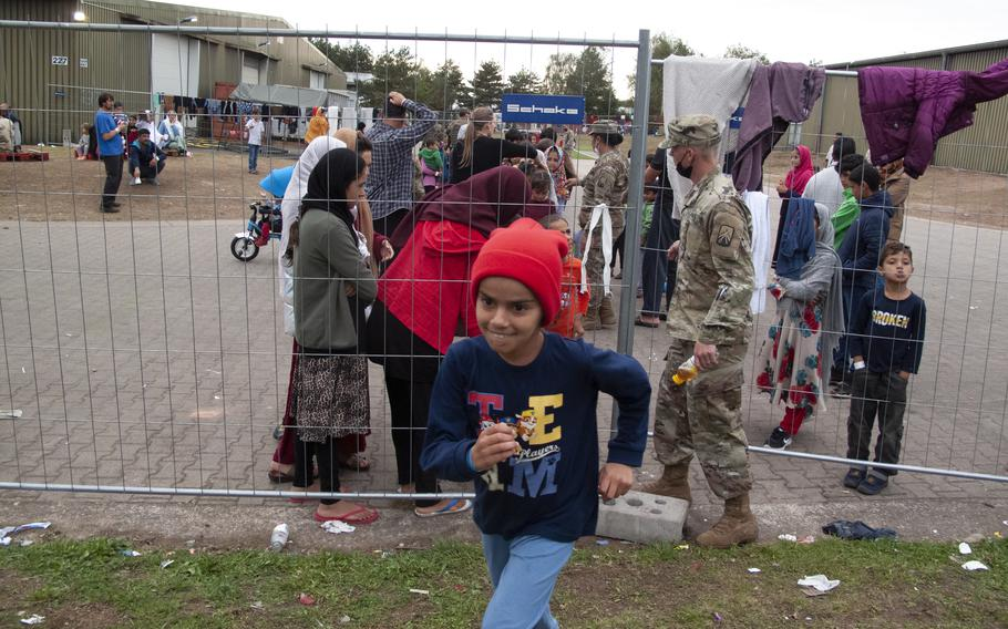 An Afghan child runs to English class after being allowed through a makeshift gate on Rhine Ordnance Barracks, Sept. 27, 2021.