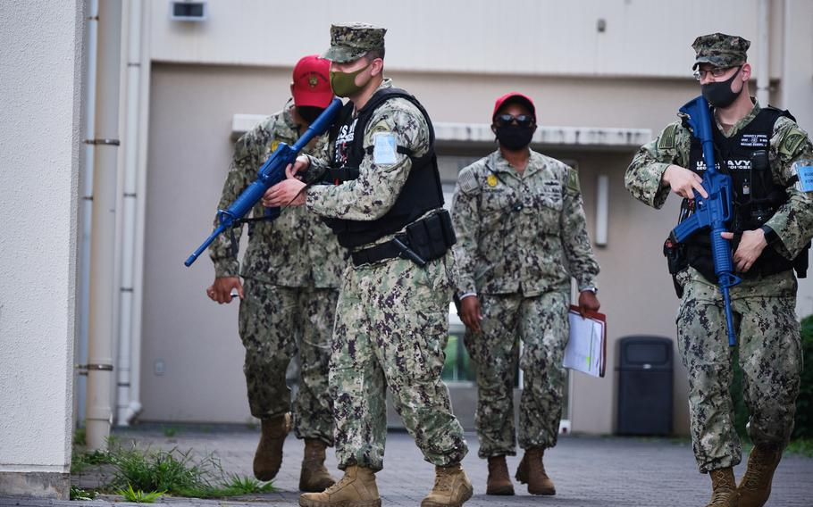 Petty Officer 1st Class James Eggers and Petty Officer 2nd Class Andres Gonzalez wield rubber M4 carbines during an active-stabber drill at the exchange at Yokosuka Naval Base, Japan, July 20, 2021. The action was part of the Citadel Pacific exercise.