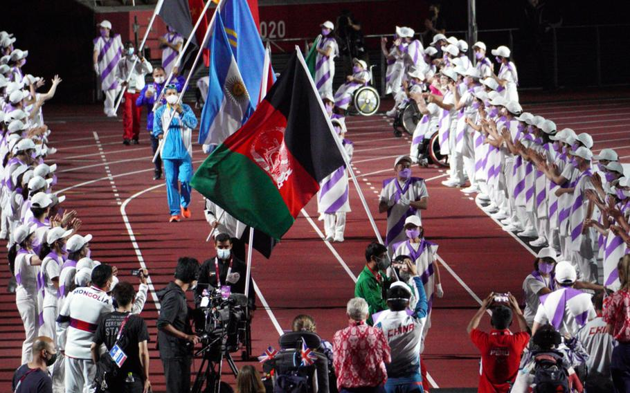 Athletes carry the Afghanistan flag during closing ceremonies for the Tokyo Paralympics at National Stadium, Sunday, Sept. 5, 2021.