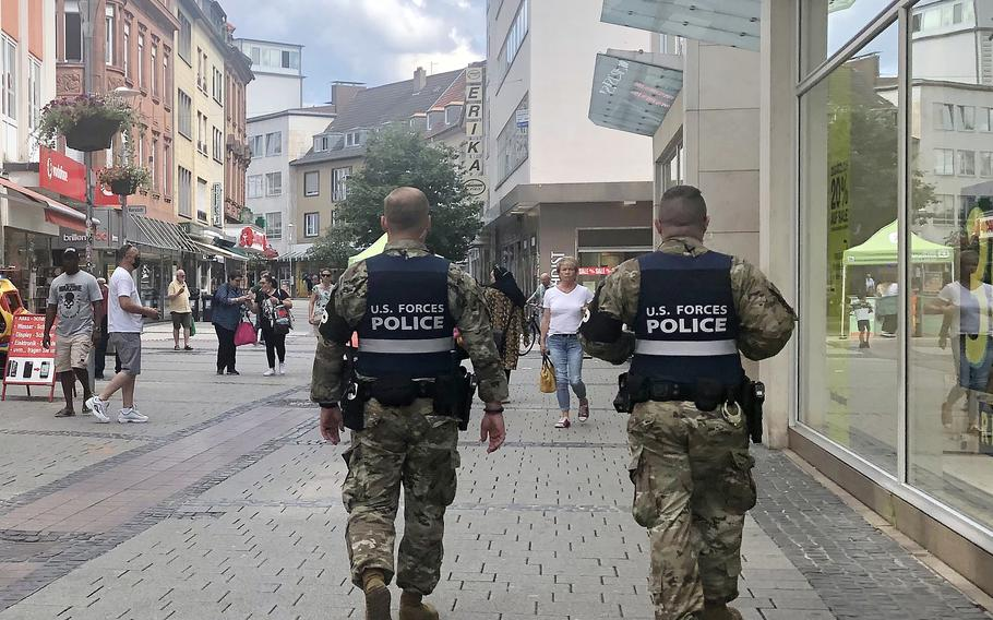 Two U.S. military policemen walk through the pedestrian zone in Kaiserslautern, Germany, on July 26, 2021. German officials have started tightening coronavirus restrictions in the city as infection rates rose.