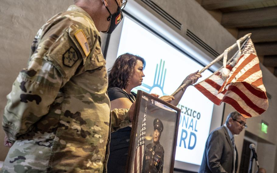 Retired Col. Brian Baca, right, tells New Mexico National Guard soldiers and airmen the incredible story of an American flag made from scraps of material in a Japanese prisoner of war camp during World War II, Sept. 8, 2021 in Albuquerque, N.M.