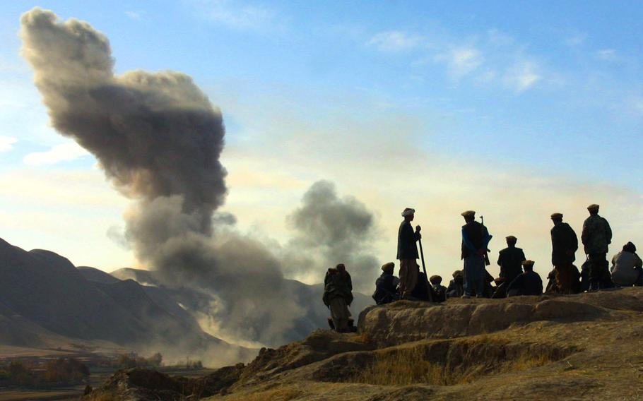 Northern Alliance soldiers watch as U.S. air strikes attack Taliban positions in Kunduz province, Afghanistan, on Nov. 19, 2001.