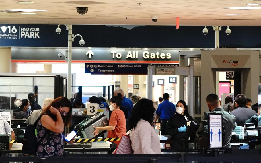 Travelers wearing protective masks are screened at a Transportation Security Administration security checkpoint at Los Angeles International Airport in Los Angeles on May 28, 2021.