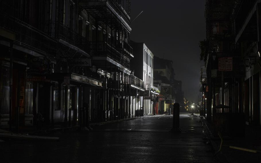 Bourbon Street in the New Orleans French Quarter is dark except for lights used during a TV broadcast Monday, Aug. 30, 2021, after New Orleans lost power during Hurricane Ida.