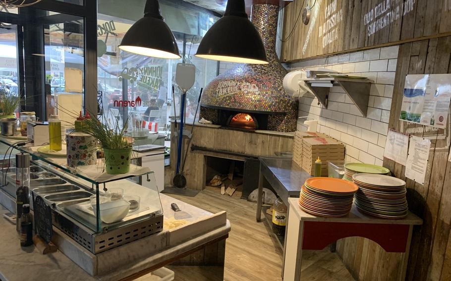 The kitchen at Johnny Take Ue features a colorful pizza oven.