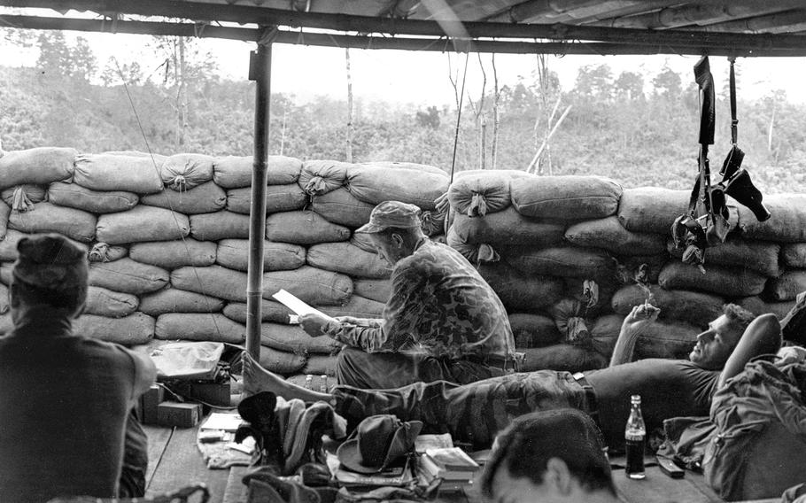 """South Vietnam, December, 1963: Staff Sgt. Howard Stevens, center, Special Forces adviser to a Montagnard strike force, reads his mail at Phey-Shuron, a camp being built in Vietnam's Central Highlands. Stevens was part of a 12-man """"A-team"""" attempting to make soldiers of Koho tribesmen in the jungle mountains west of Dalat."""