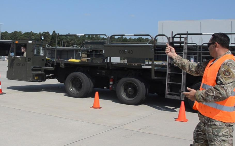 A judge in the 721st Aerial Port Squadron's Multi-Capable Airmen Rodeo at Ramstein Air Base on July 23, 2021, tells Airman 1st Class Ryan Joy to keep driving during an exercise in which competitors drive a Tunner 60K aircraft cargo loader through a course with figure eights and coned-off sharp turns and straightaways.