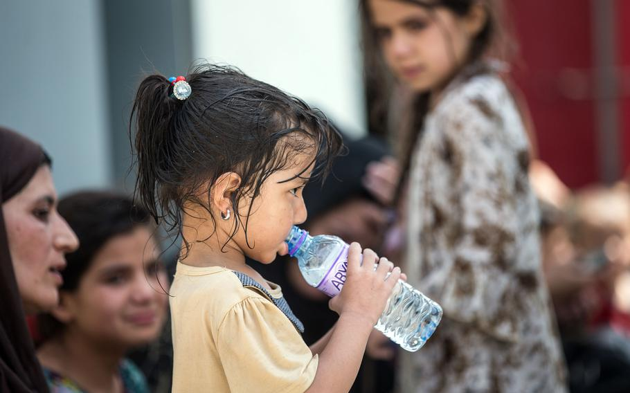 An Afghan child sips water at Hamid Karzai International Airport in Kabul, Afghanistan, Aug. 20, 2021.