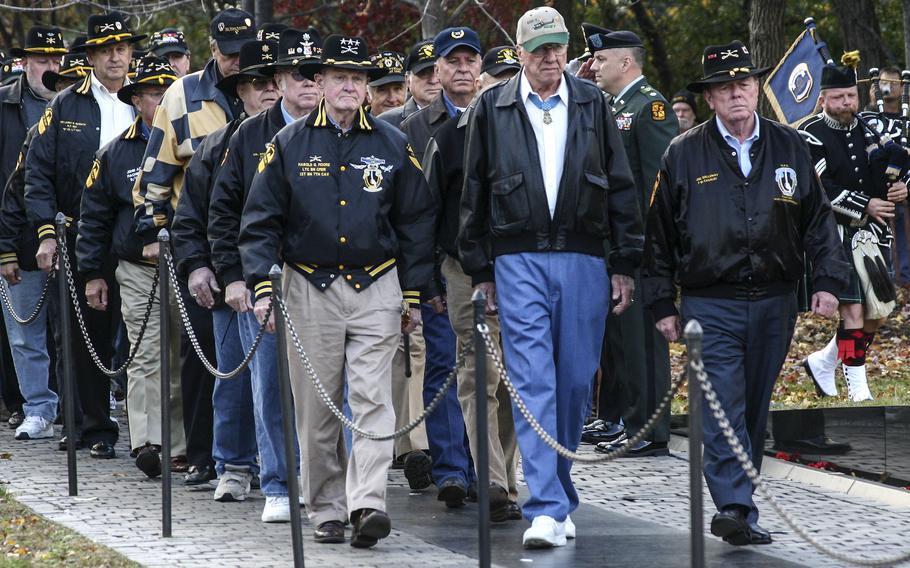 """Medal of Honor recipient Ed """"Too Tall"""" Freeman, front center, Hal Moore, front left, and Joe Galloway lead a group of Ia Drang battle survivors during a 2005 ceremony at the Vietnam Veterans Memorial in Washington in 2005."""